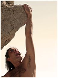 Rock climber hanging on by his fingertips